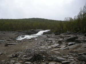 Silbojokks utlopp i sjön Sädvajaur, där silverhyttan låg till vänster om forsen. Kyrkan och kyrkogården återfinns hitom forsen, närmast i bild.