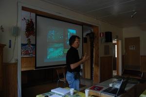 Olof pratar om Aareavaaraboplatserna med powerpoint-bild i bakgrunden. Foto: Frida Palmbo © Norrbottens museum