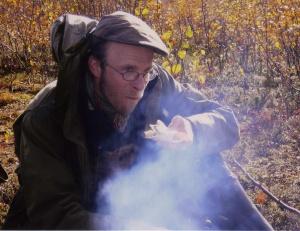 En inrökt arkeolog vid lägereld under lunchpaus. Lars Backman njuter av en smörgås i röken. Fotograf: Olof Östlund