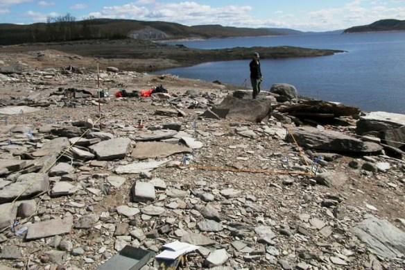 Undersökningsområdet (2004) är täckt med ett lager svallat grus. Ena hörnet av kyrkogrunden syns till vänster i bild. Arkeolog Jonas Hägg är med på bilden.