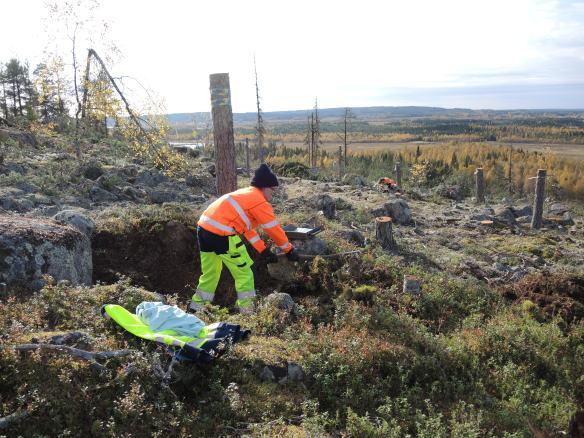 Arkeolog Olof Östlund avtorvar en av groparna i klapper på Öberget © Norrbottens museum