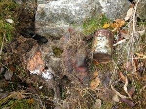 Källargrop fylld med skräp, här en sko, en flaska och en plåtburk.