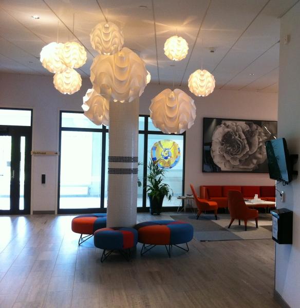 """Entrén på Hotell Vistet. Ovanför soffan Kolteckningen """"Rosen"""" (2014) av Agneta Andersson och i glasgången en målning från 2015 av Ulrika Tapio Blind. Foto: Henrik Ygge © Norrbottens museum"""