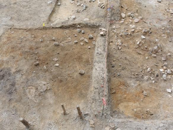 Nedgrävning av det stora fyndförande området med mörkbruna färgningar, brända ben och skörbränd sten © Norrbottens museum