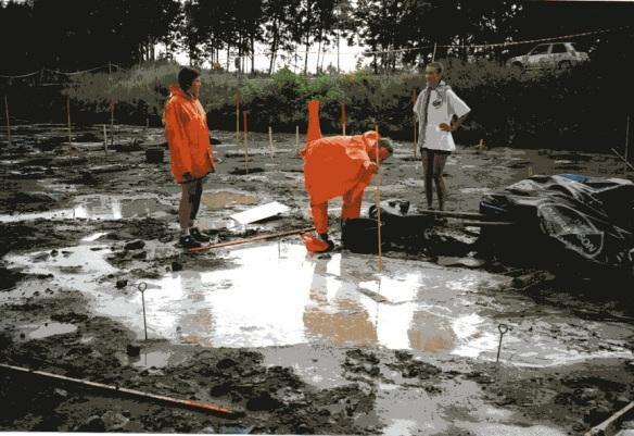 Blött grophus i Barva. Arbetskompisarna mäter djupet på vattnet. Foto från Olof Östlunds privata fotoalbum