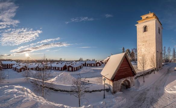 Gammelstads kyrkby i vinterskrud med kyrkans klocktorn till höger och kyrkans bogårdsmur i förgrunden. Foto Daryoush Tahmasebi © Norrbottens museum.