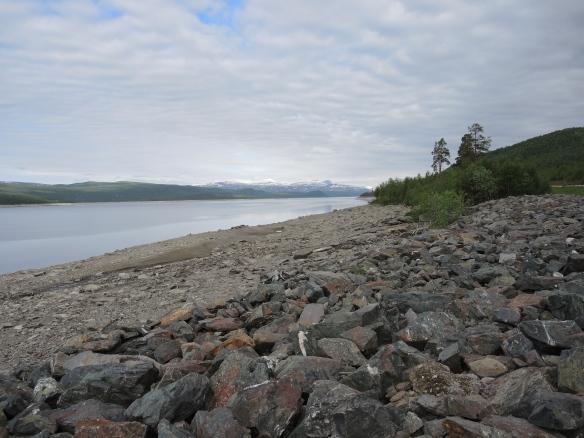 Erosionskanten längs Sädvajaures stränder är inte vacker, men ovanför ses skir grönska och snöklädda fjäll i bakgrunden. En bit ovanför vattnet anas den gamla vägen.
