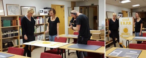 en person filmar två personer tittar på en fana