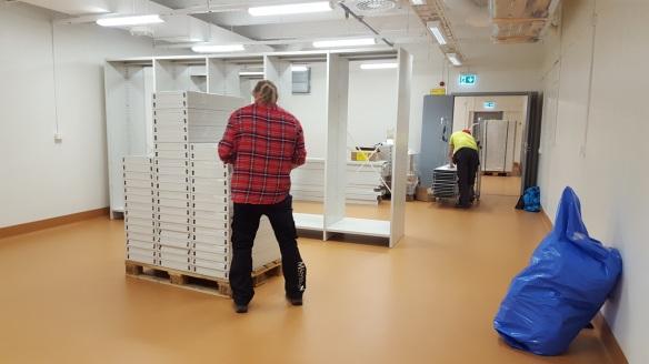 Två män arbetar med att montera arkivhyllor