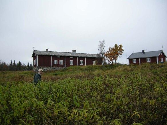 foto med en man i hög vegetation och ett hus i bakgrunden