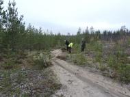 Cadja, Gunilla Lindbäck, Frida Palmbo och Åke Naalisvaara på den förmodade boplatsvallen, med körspår rakt igenom anläggningen.