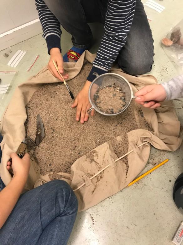 Foto på fiktiv arkeologisk undersökning. sand med gömda fynd i ett klassrum.