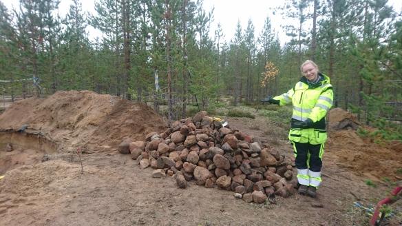 En arkeolog bredvid en stor hög med stenar som lyfts upp ur en undersökt kokgrop