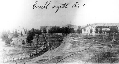 Svartvitt foto över äldre bebyggelse och landsväg.
